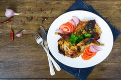 Fried rabbit legs on a white plate on a wooden table. Dietary rabbit meat. Cooked on the grill Stock Photos