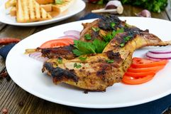Fried rabbit legs on a white plate on a wooden table. Dietary rabbit meat. Cooked on the grill Royalty Free Stock Photos