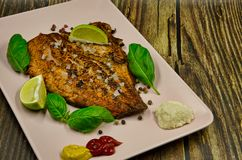 Fried rainbow trout steak. Fried rainbow-pepper steak with pepper, salt mustard and ketchup, garnished with basil leaves and pieces of lime, served on a pink royalty free stock images