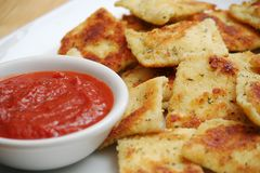 Fried Ravioli and Marinara Sauce. Fried Ravioli on White Plate With a Bowl of Marinara Sauce Royalty Free Stock Photos