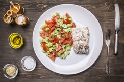 Fried red fish with sauce and garnished with vegetable salad on white plate with spices vintage knife and fork on wooden rusti Stock Photos