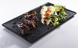 Fried ribs with mashed potatoes  isolated on white. Roasted ribs with mashed potatoes seasoned with honey sauce on square black plate isolated on white stock image