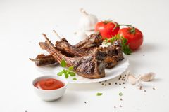 Fried ribs on a plate with tomato sauce on white Stock Photo