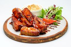 Fried ribs. Fried pork ribs on a wooden plate decorated with salad royalty free stock images