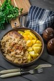 Fried ribs in sauerkraut. Fried ribs in sauerkraut served with roasted potatoes Stock Images