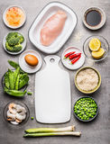 Fried rice cooking ingredients with chicken , egg , shrimps and green vegetables around white cutting board Stock Photo