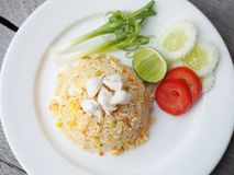 Fried rice with crab meat. Top view of fried rice with crab meat served in white plate decoration with vegetable, cucumber, tomato and lemon. On gray wooden Stock Image