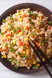 Fried rice with eggs, corn and parsley closeup vertical top view Royalty Free Stock Photo
