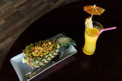 Fried rice inside pineapple next to a glass of juice with a straw and slices of fruit. stock image