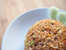 Fried Rice mit Huhn, Gurke und Petersilie auf weißem Teller, hölzerne Tabelle, thailändische Küche Lizenzfreie Stockfotos