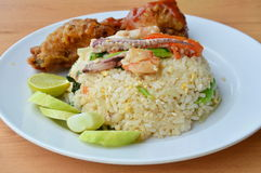 Fried rice with mixed seafood and crispy chicken on plate. Fried rice with mixed seafood and crispy chicken on white plate Royalty Free Stock Image