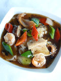 Fried rice noodles with fish cutlet and shrimps in black bean sauce Stock Photo