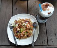 Fried rice noodles Thai traditional dishes on old wooden table stock photos