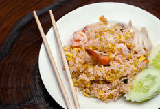 Fried rice with seafood and sliced cucumber. On white plate and wooden background Stock Images