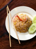 Fried rice with seafood and sliced cucumber. On white plate and wooden background Stock Photography