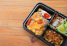 Fried rice with shrimp paste include mango, egg, pork, onion, vegetable in box black Thai style food on a wood table background.  Stock Image