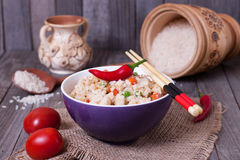 Fried rice with vegetables in a bowl. On a wooden table Stock Images