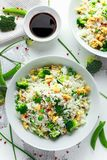 Fried rice with vegetables, broccoli, peas and eggs in a white bowl. soy sauce. healthy food stock image