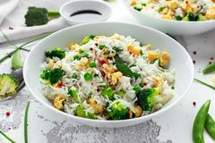 Fried rice with vegetables, broccoli, peas and eggs in a white bowl. soy sauce. healthy food royalty free stock photos