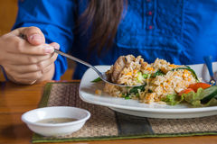 Fried rice. Woman using spoon eating pork fried rice on table Stock Photo