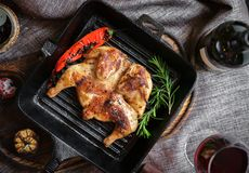 Fried roast chicken in a frying pan on a wooden Board. In the table, top view royalty free stock images
