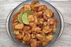 fried roasted shrimps in plate with lime pils in a big glass plate on grey background stock images