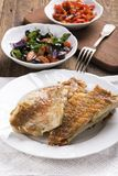 Fried rose fish fillet on a white plate stock photos