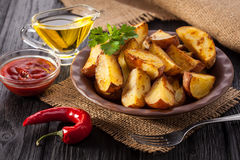 Fried rosemary potato wedges in a rustic setting. Stock Image