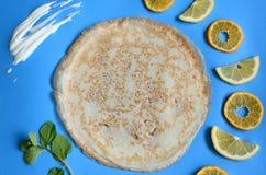 Pancake on blue cardboard background Pieces of fruit. Maslenitsa. Fried round pancake on a blue cardboard background with pieces of fruit. Picture. Maslenitsa stock photos