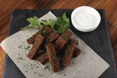 Fried rye croutons. With garlic sauce on a slate. Wooden background Stock Image