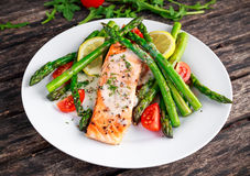Fried salmon with asparagus, tomatoes, lemon, yellow lime on white plate.  Royalty Free Stock Photography