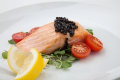 Fried Salmon With Black Caviar. Close up of delicious pan fried salmon with fresh black caviar, tomatoes, and microgreens salad. Elite food Royalty Free Stock Photo