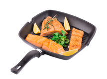 Fried salmon fillet in pan with lemon. Royalty Free Stock Photos