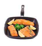 Fried salmon fillet in pan with lemon. Royalty Free Stock Photography