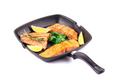 Fried salmon fillet in pan with lemon. Stock Photo