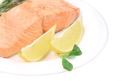Fried salmon fillet on plate with lemon. Royalty Free Stock Photo