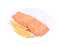 Fried salmon fillet on plate with lemon. Isolated on a white background Royalty Free Stock Images