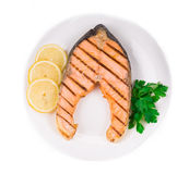 Fried salmon fillet on plate with lemon. Isolated on a white background Royalty Free Stock Photo