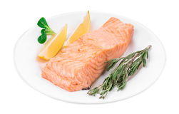 Fried salmon fillet on plate with lemon. Isolated on a white background Stock Photos