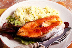 Fried salmon and herby couscous aside Royalty Free Stock Images