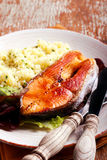 Fried salmon and herby couscous aside Stock Photo