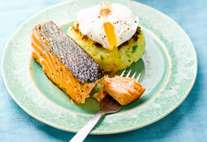 The fried salmon with a potato patty and poached egg Stock Photography