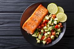 Fried salmon steak with avocado tomato salsa closeup. Horizontal. Fried salmon steak with avocado tomato salsa closeup on a plate. horizontal top view from above stock image