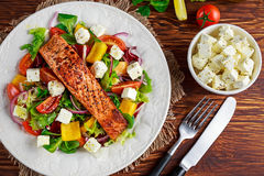 Fried Salmon steak with fresh vegetables salad, feta cheese. concept healthy food. Royalty Free Stock Photos