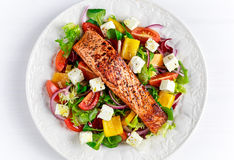 Fried Salmon steak with fresh vegetables salad, feta cheese. concept healthy food. Royalty Free Stock Image