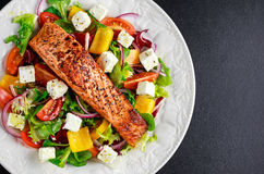 Fried Salmon steak with fresh vegetables salad, feta cheese. concept healthy food. Stock Photos