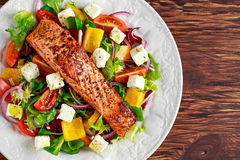 Fried Salmon steak with fresh vegetables salad, feta cheese. concept healthy food. Royalty Free Stock Images