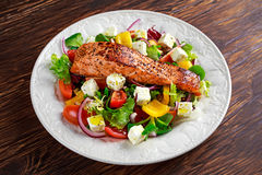 Fried Salmon steak with fresh vegetables salad, feta cheese. concept healthy food. Stock Images