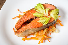 Fried salmon steak with vegetables on plate Royalty Free Stock Images