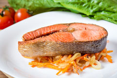 Fried salmon steak with vegetables on plate Royalty Free Stock Image
